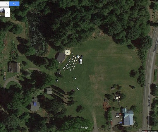 Worthington Park aerial view, set up for a 2014 private event. Museum is at lower right with blue roof. Linger Longer Stage dance floor is white circle at center with tables, tents and umbrellas. Center Road at right, Columbia Street at bottom.